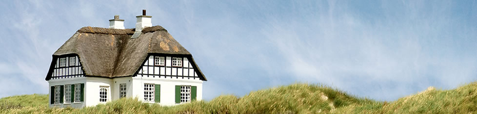 Dünenlandschaft mit reetgedeckten Fachwerkhaus auf der linken Seite